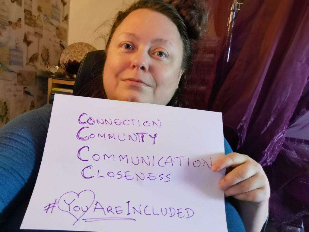 Person holding up sign with the text: connection, community, communication, closeness, #YouAreIncluded