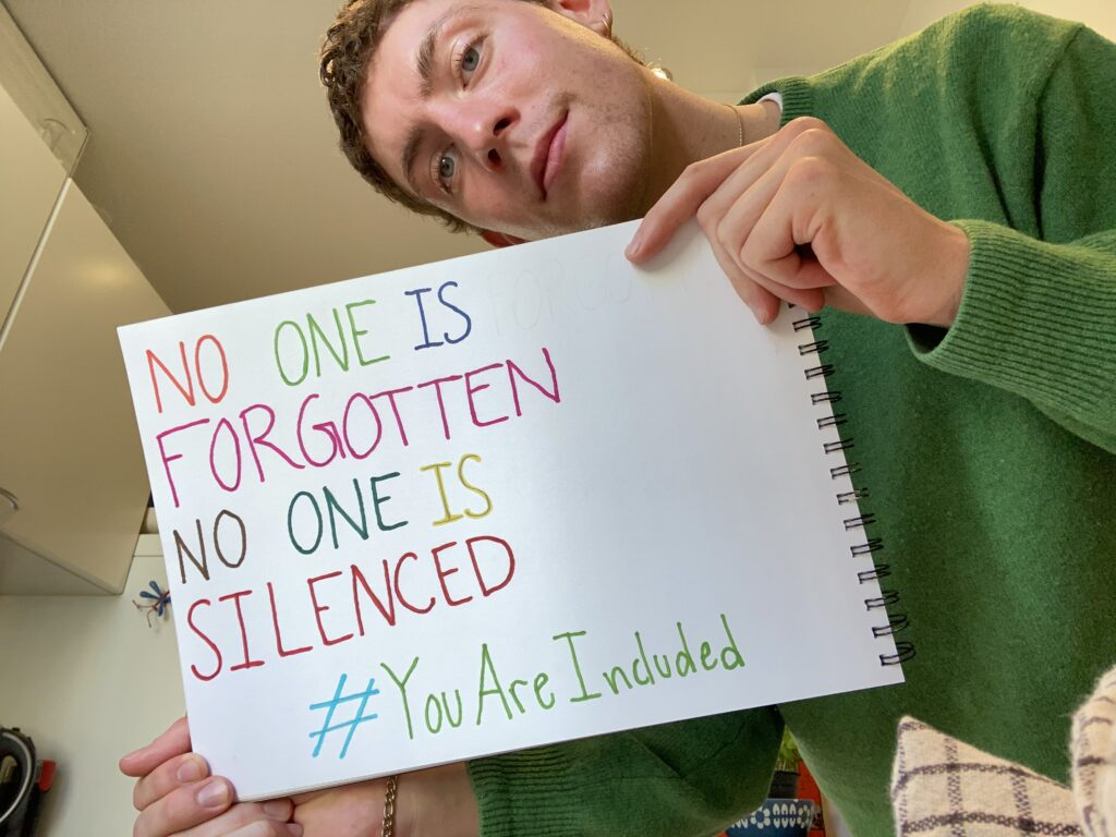 Guy holding up a sign saying: No one is forgotten, no one is silenced. #YouAreIncluded